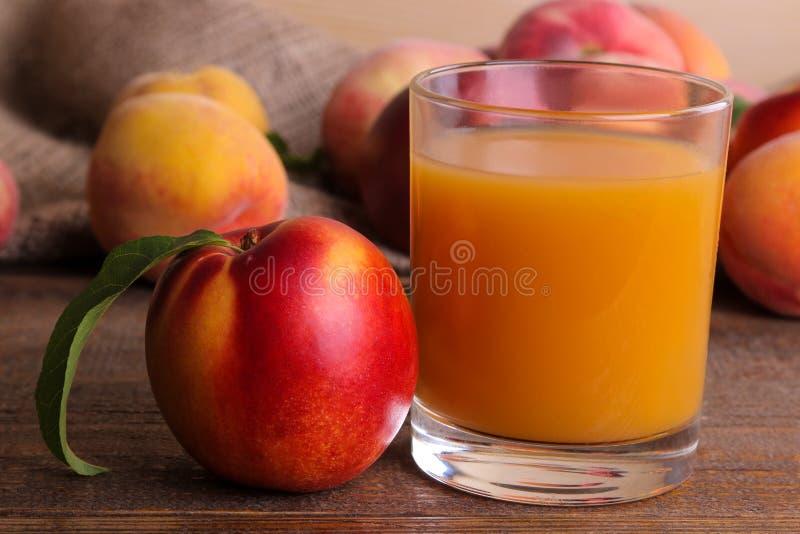 在一块玻璃的桃子汁在棕色木背景的一个桃子特写镜头旁边 库存照片