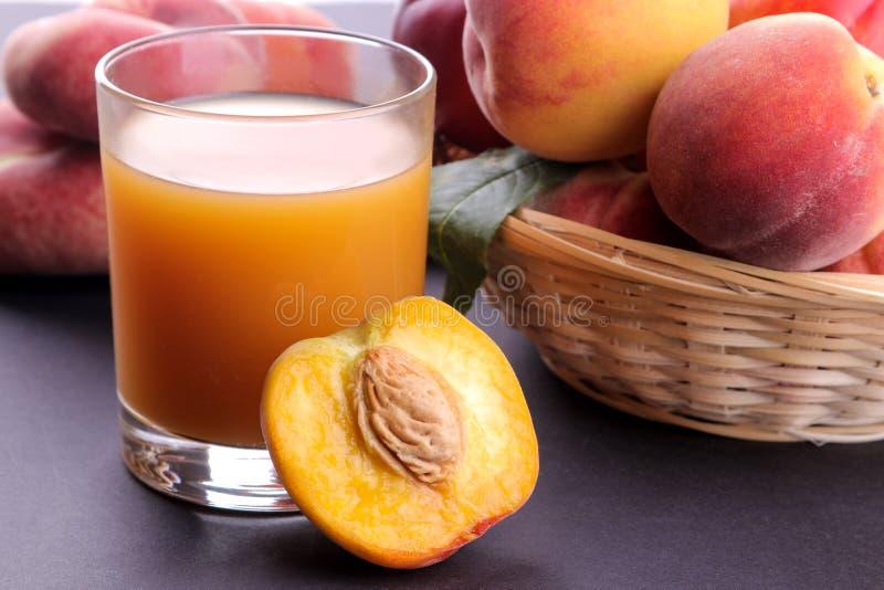 在一块玻璃的桃子汁在黑暗的背景的一个新鲜的桃子特写镜头旁边 库存图片