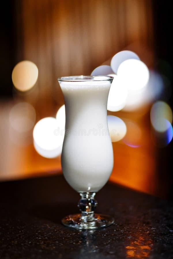 在一块玻璃的白色奶昔在腿 免版税库存照片