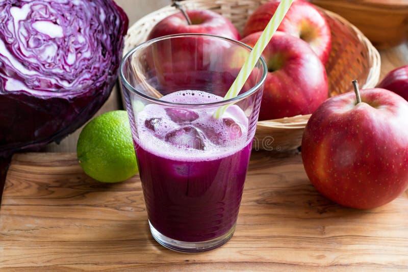 在一块玻璃的紫色圆白菜汁在一张木桌上 库存图片