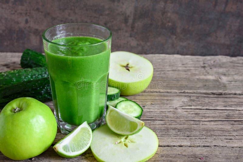 在一块玻璃的绿色健康圆滑的人用菠菜、苹果、黄瓜和石灰在土气木桌 戒毒所饮料 免版税库存图片