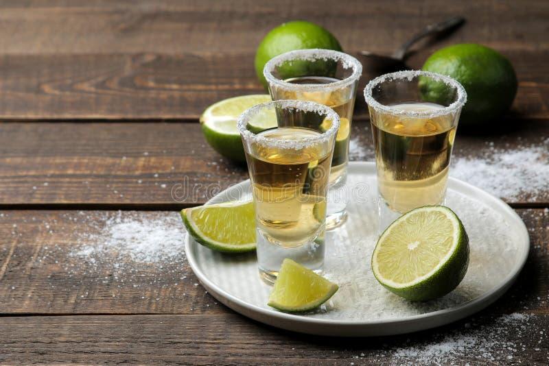 在一块玻璃的金子龙舌兰酒与盐和石灰在一张棕色木桌上 酒精饮料 免版税库存照片