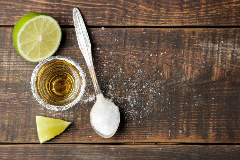 在一块玻璃的金子龙舌兰酒与盐和石灰在一张棕色木桌上 酒精饮料 r 免版税库存图片