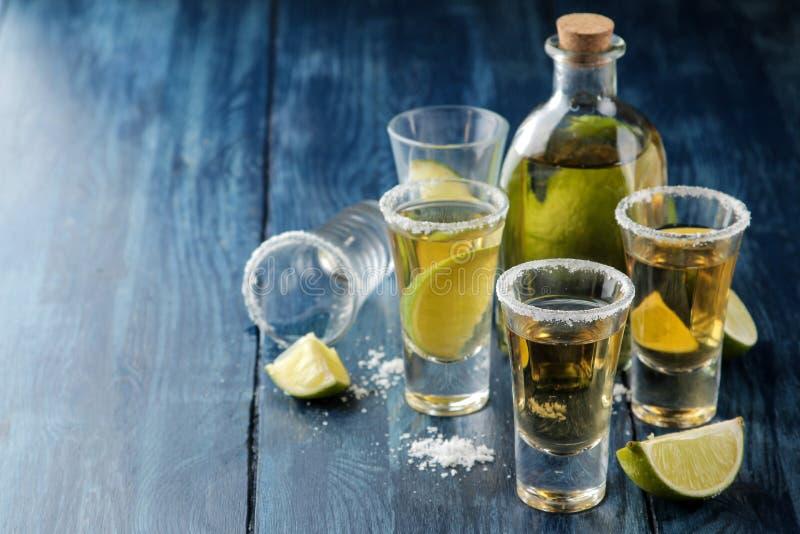 在一块玻璃的金子龙舌兰酒与盐和石灰在一张蓝色木桌上 酒精饮料 图库摄影