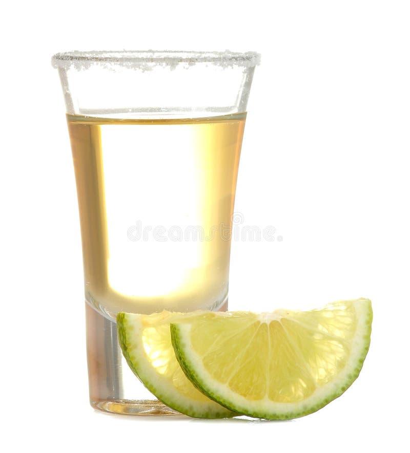 在一块玻璃的金子龙舌兰酒与盐和石灰在白色被隔绝的背景 酒精饮料 r 免版税图库摄影