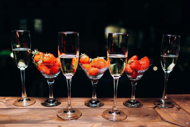在一块玻璃的香宾用草莓在夜 免版税库存图片
