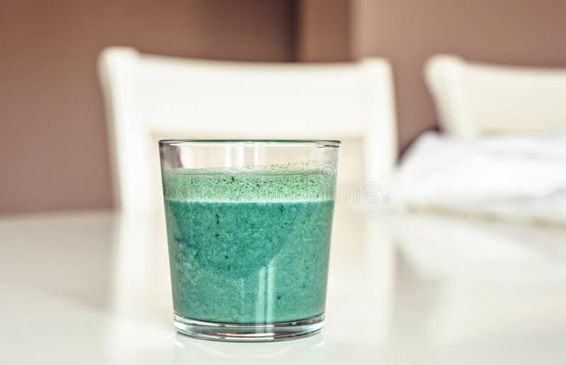 在一块玻璃的Spirulina震动在白色桌上 免版税库存照片