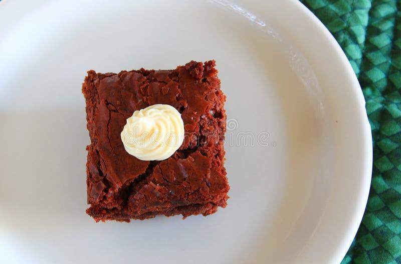 在一块白色板材的乳脂软糖果仁巧克力 免版税库存图片