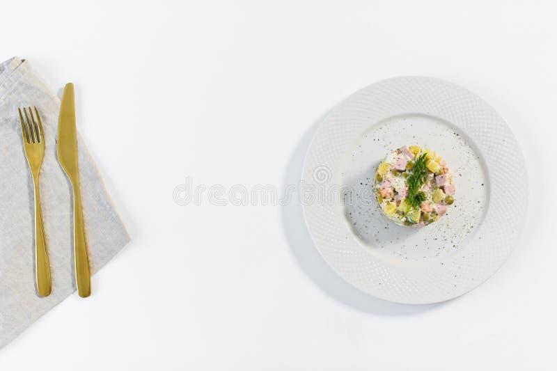 在一块白色板材的俄国在白色背景的沙拉有一把金黄刀子的和叉子 免版税库存照片