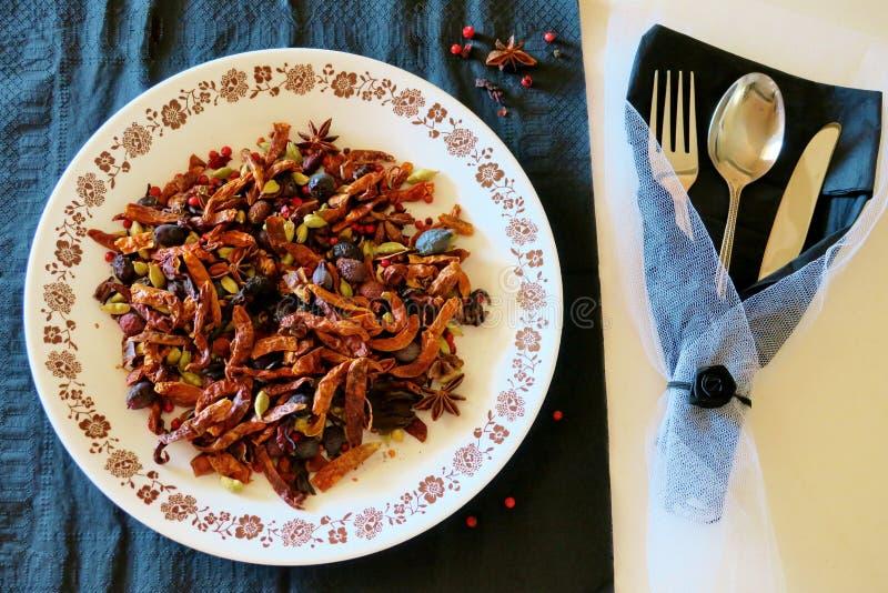 在一块白色板材的各种各样的辣的香料在厨房匙子、叉子和刀子旁边 免版税库存图片