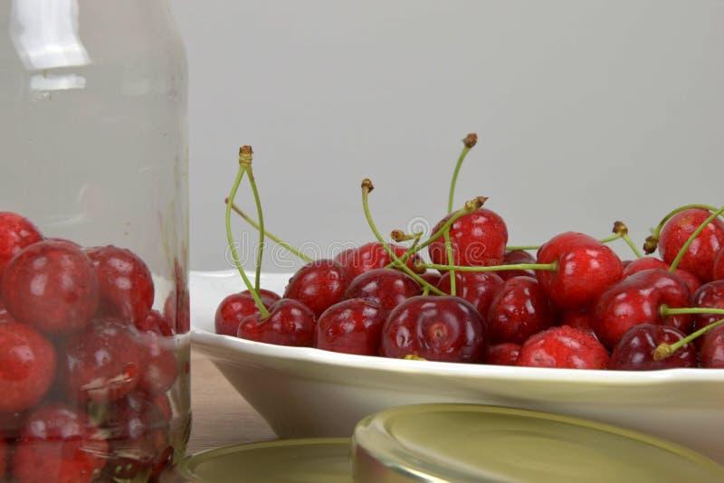 在一块白色板材的成熟红色樱桃在一张木桌上 自创樱桃瓶子 奶油被装载的饼干 图库摄影