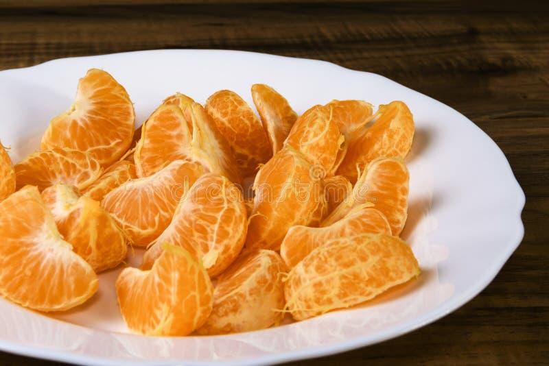 在一块白色板材的新蜜桔切片 免版税库存照片