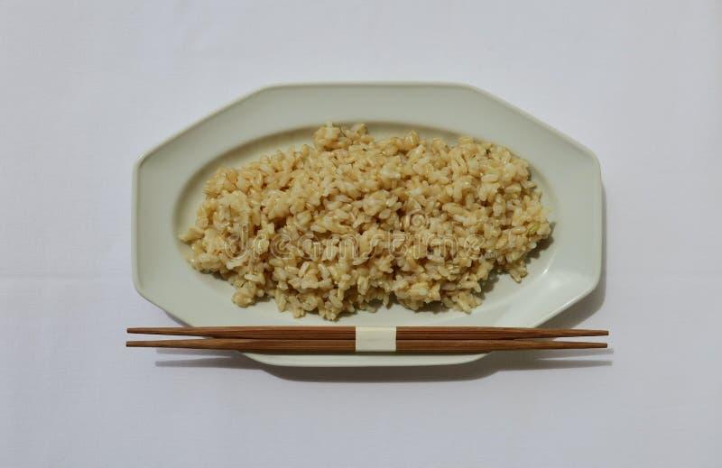 在一块白色板材的未磨光的糙米有筷子的 库存图片