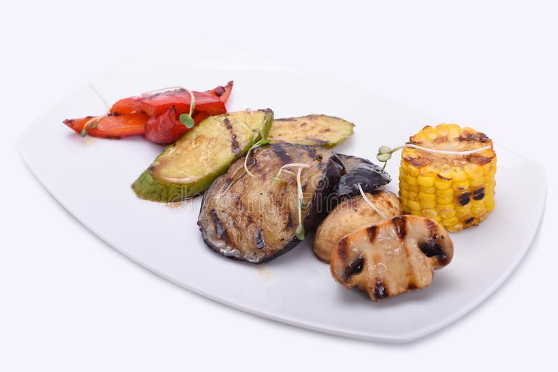 在一块白色板材的烤菜-茄子、夏南瓜、蘑菇、玉米和红色甜椒 库存图片