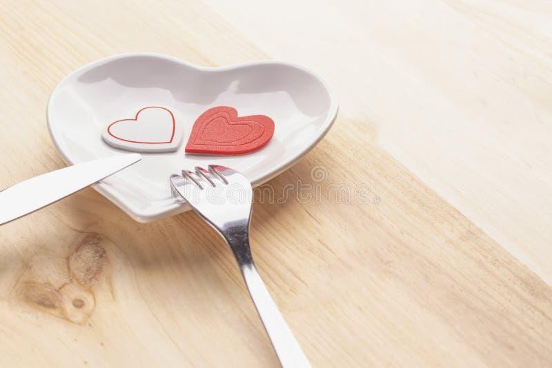 在一块白色板材的红心以在木背景的心脏的形式与叉子和刀子 图库摄影