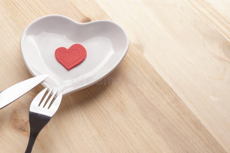 在一块白色板材的红心以在木背景的心脏的形式与叉子和刀子 库存照片