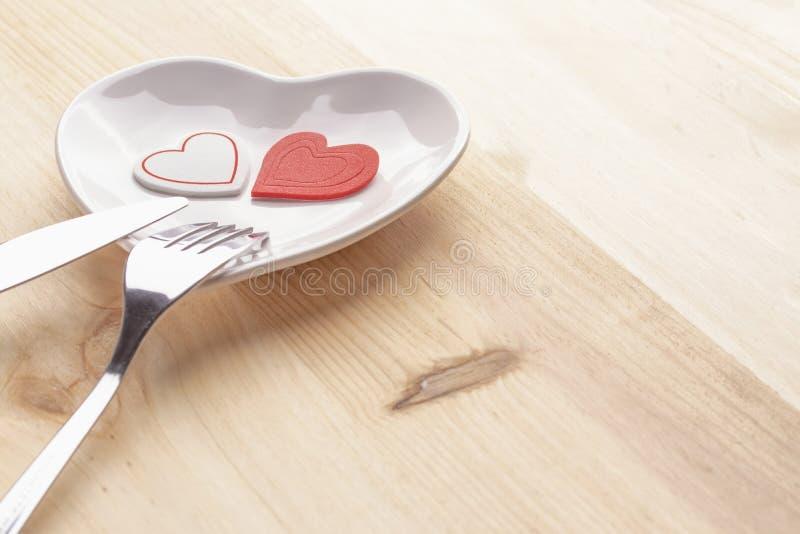 在一块白色板材的红心以在木背景的心脏的形式与叉子和刀子 免版税图库摄影