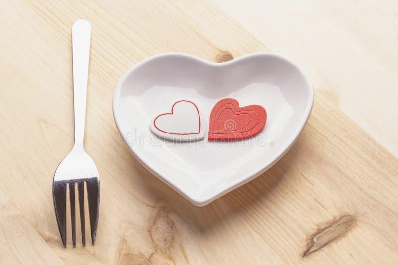 在一块白色板材的红心以在木背景的心脏的形式与叉子和刀子 免版税库存照片