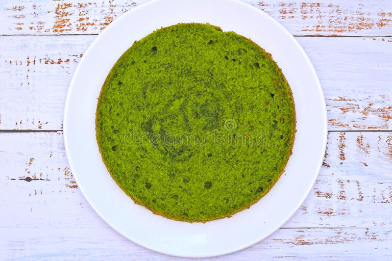 在一块白色板材的绿色圆的菠菜薄菏蛋糕在与破旧的委员会的桌上 库存图片