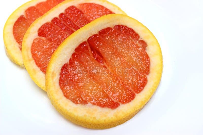 在一块白色板材的葡萄柚切片 免版税库存图片