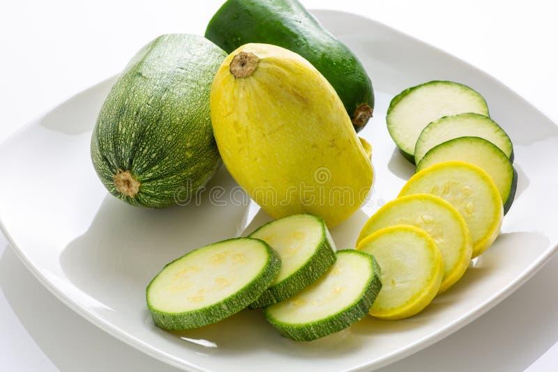 在一块白色板材的被切的黄色和绿色夏南瓜` s坐等待的厨房用桌被消耗 免版税库存图片