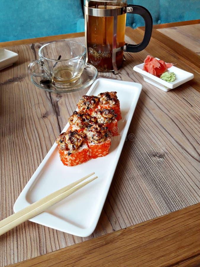 在一块白色板材的被烘烤的海鲜卷有筷子、姜和山葵的在一张木桌上 免版税库存图片