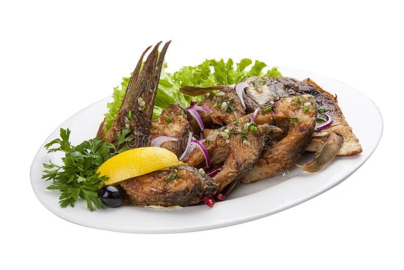 在一块白色板材的被烘烤的鲤鱼 免版税库存照片