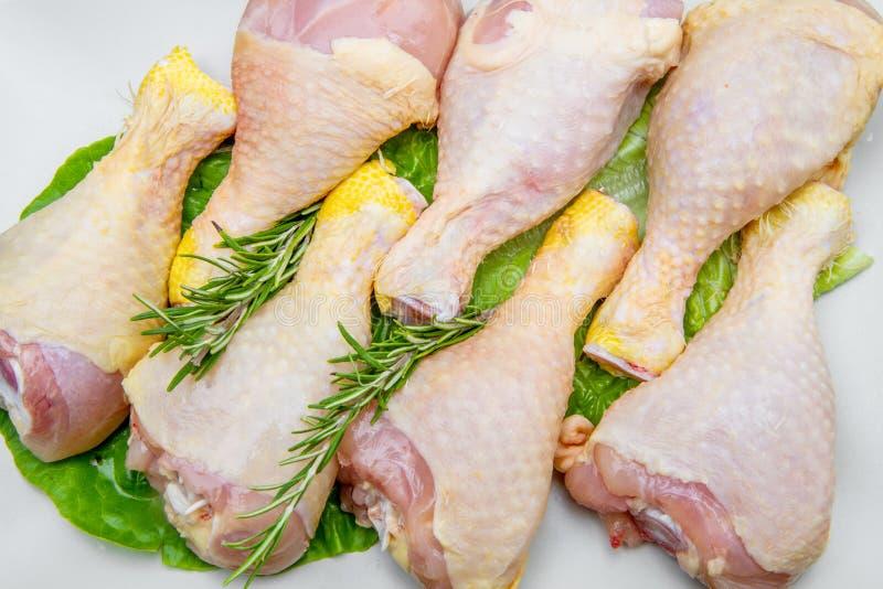 在一块白色板材的鸡大腿在黑木桌上 免版税库存图片