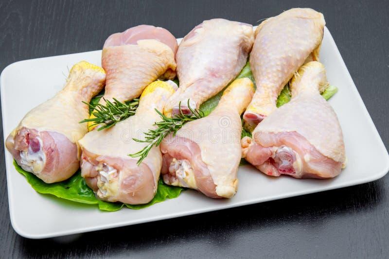 在一块白色板材的鸡大腿在黑木桌上 免版税图库摄影