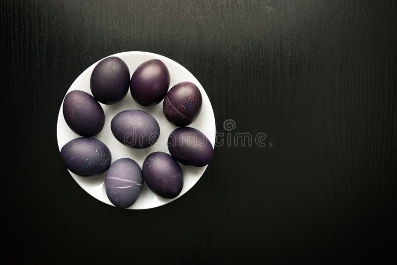 在一块白色板材的紫罗兰色复活节彩蛋,在一黑木backgroun 库存图片