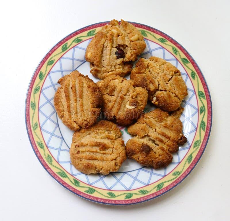 在一块相当装饰板材的六个自创花生酱曲奇饼在从上面观看的白色桌上 库存图片