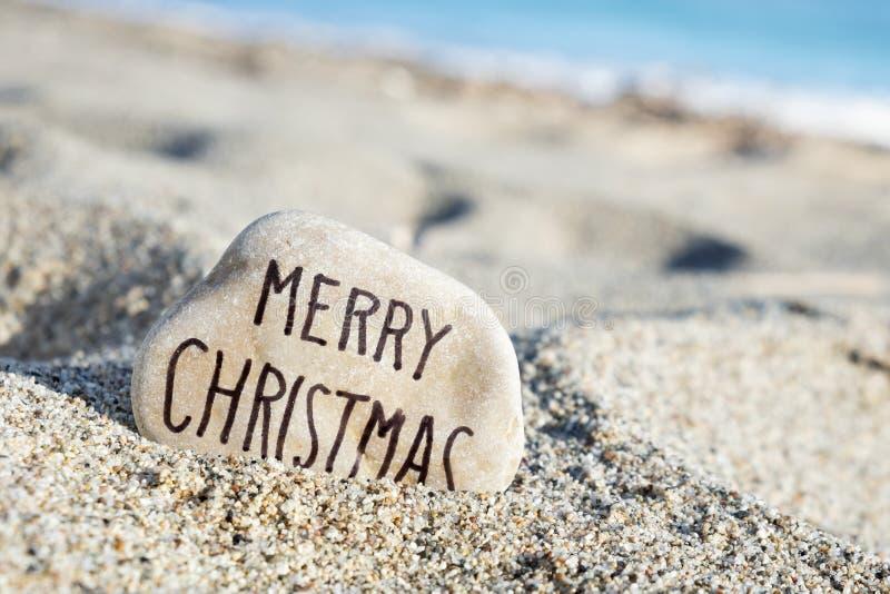 在一块石头的文本圣诞快乐在海滩 库存图片