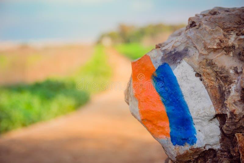 在一块石头(以色列足迹)绘的供徒步旅行的小道标志在乡下区域 免版税库存图片