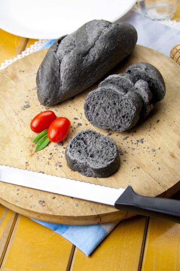 在一块砧板切的黑碳面包 图库摄影