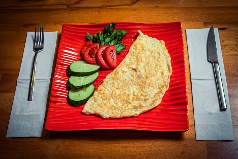 在一块红色时髦的板材和一杯的全国盘在一张木桌上的黑土耳其茶 免版税库存图片