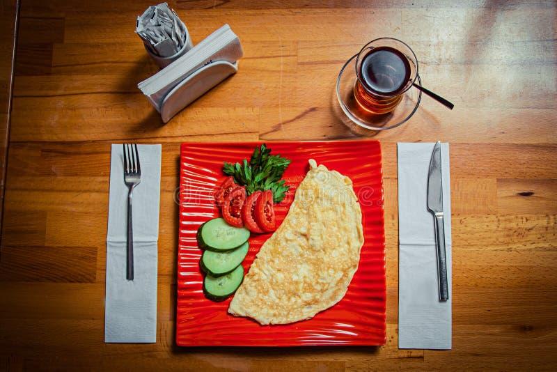在一块红色时髦的板材和一杯的全国盘在一张木桌上的黑土耳其茶 库存图片