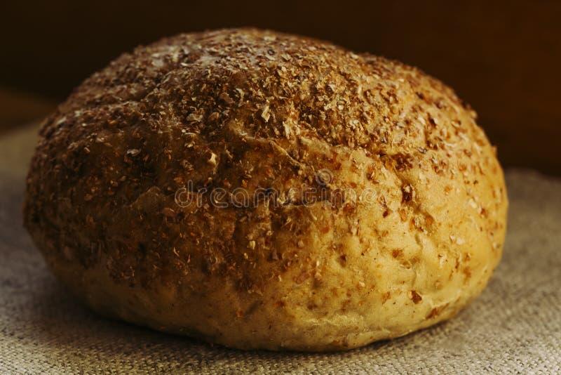 在一块自然蓝色纺织品餐巾的黑麦面包谎言,健康食品的概念大面包  免版税库存照片