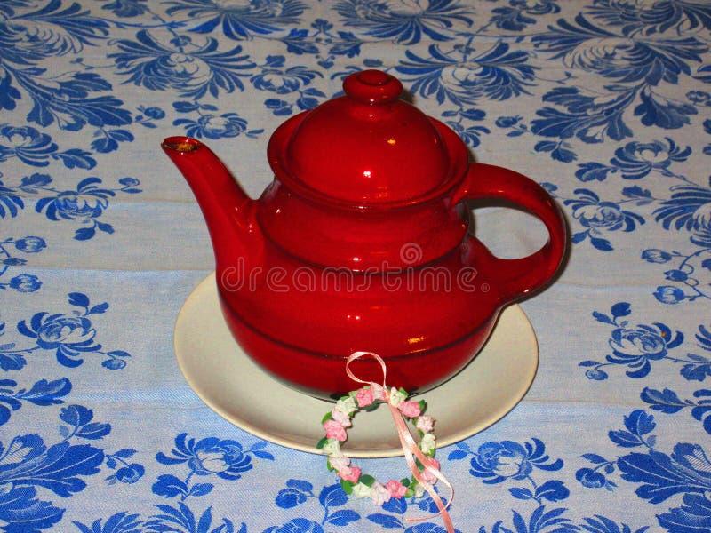 在一块蓝色开花的帆布的秀丽红色茶罐 免版税库存图片