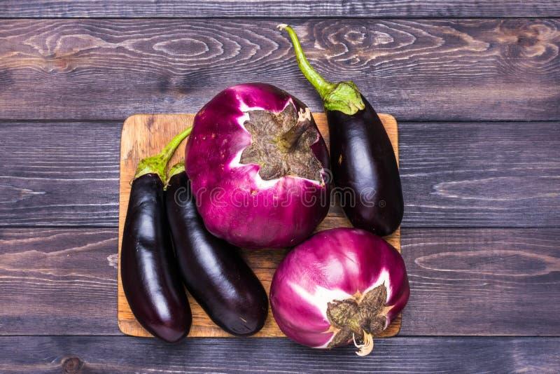在一块蓝色板材的新鲜的未加工的紫色茄子在灰色木背景 顶视图,空白 从茄子舱内甲板被放置的顶视图的食谱 免版税库存照片