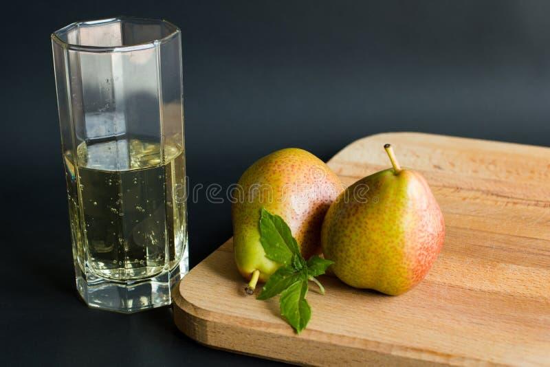 在一块透明玻璃和两个梨的软的非酒精梨萍果汁与在木切板的新鲜的蓬蒿叶子 免版税图库摄影