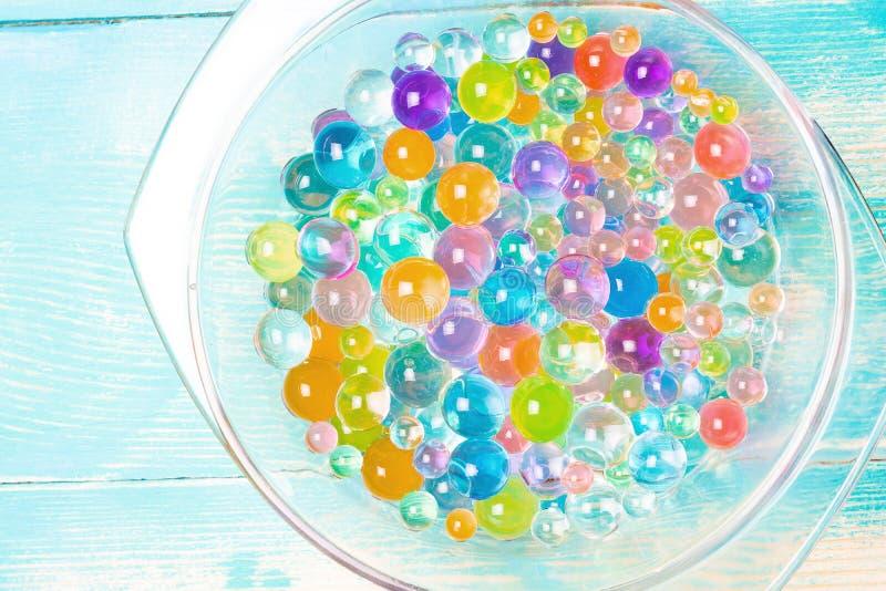 在一块透明玻璃板的多彩多姿的圆的橡胶球在一张蓝色木桌上 免版税库存图片