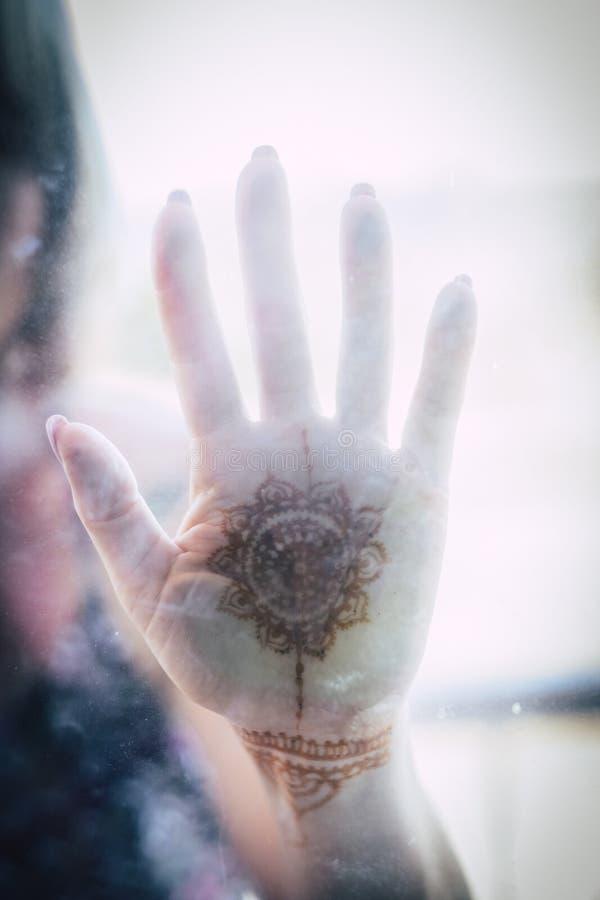 在一块透明玻璃的白种人亚洲手与被绘的坛场 传统设计和文化概念 生活和爱消息 免版税库存照片