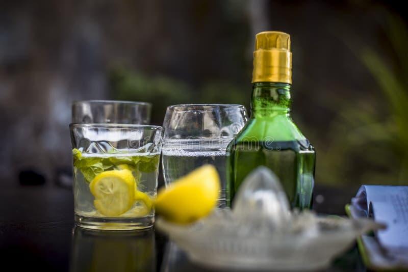 在一块透明玻璃的Mojito饮料木表面上用白色兰姆酒、苏打、柠檬汁、新鲜薄荷叶子、冰块和糖,关闭 免版税图库摄影
