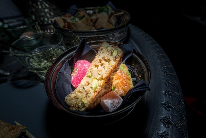在一块陶瓷板材的可口摩洛哥甜点在一个金属盘子有黑背景 库存图片
