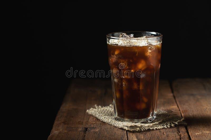 在一块高玻璃和咖啡豆的冰冻咖啡在一张老土气木桌上 在黑暗的背景的冷的夏天饮料 免版税库存图片