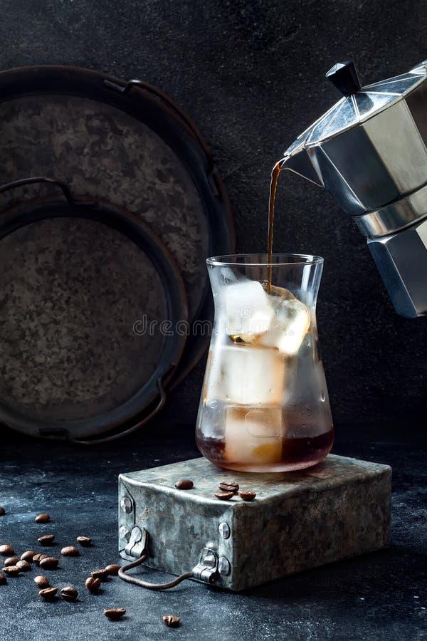 在一块高玻璃和咖啡豆的冷的刷新的冰冻咖啡在黑暗的背景 从moka罐的倾吐的咖啡到与冰的玻璃里 图库摄影