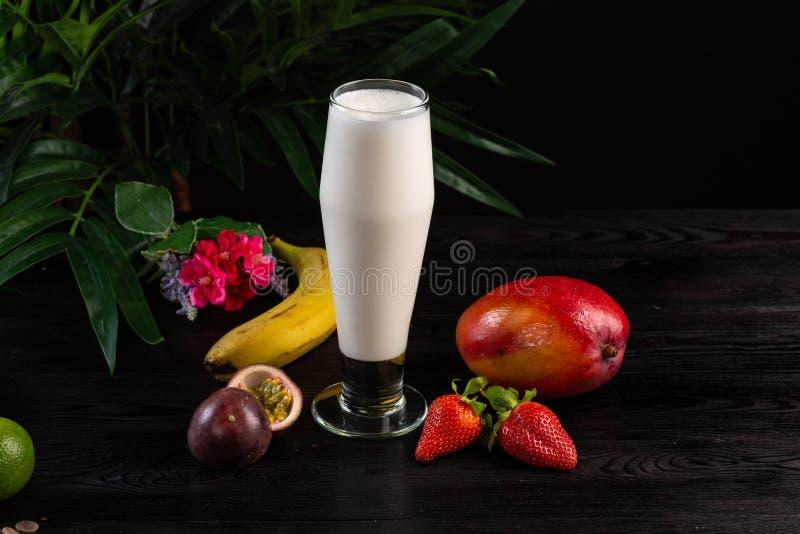 在一块高玻璃和果子的奶昔在黑暗的背景 库存照片