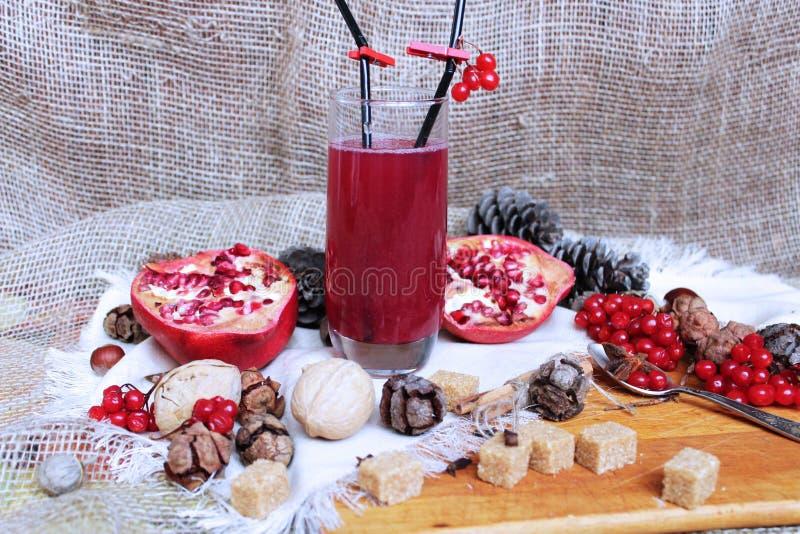 在一块高玻璃和秋天果子的莓果饮料 侧视图 库存照片