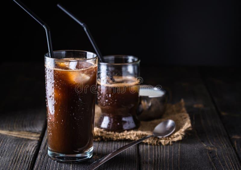 在一块高玻璃的冰冻咖啡在黑暗的自然书桌上 库存图片