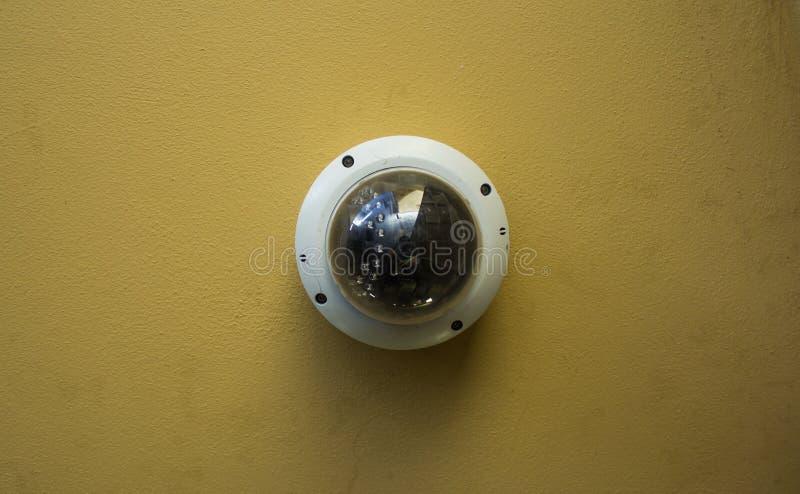 在一块黄色天花板的现代圆的安全监控相机 免版税图库摄影